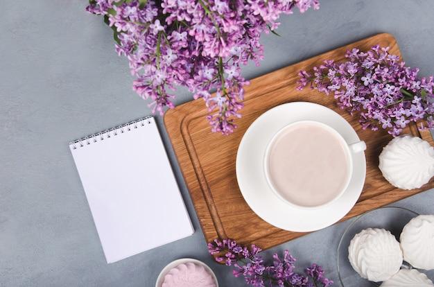 Lila, koffiekopje met latte kunst en marshmallow op witte houten tafel. plat liggen