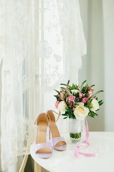 Lila sandalen op een witte tafel naast het boeket van een bruid