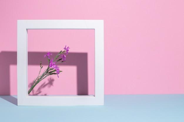 Lila wilde bloemen in een vierkant wit frame, een presentatiepodium op een roze-blauwe achtergrond.