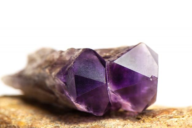 Lilac violetkleurig kristal op witte achtergrond, sluit omhoog.