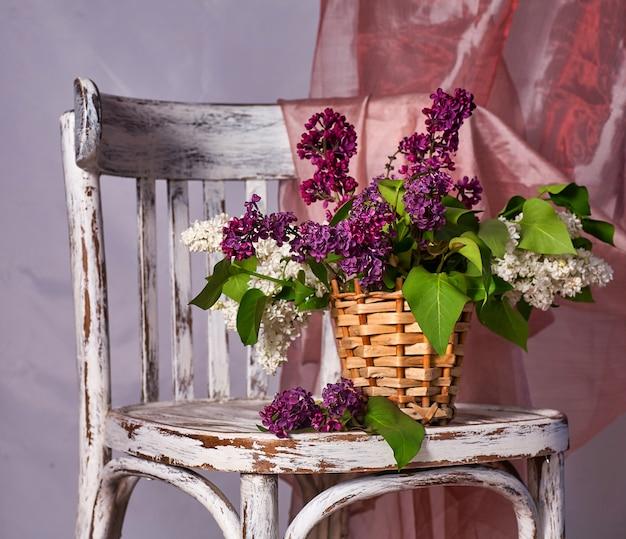 Lillac boeket in vaas op vintage houten stoel