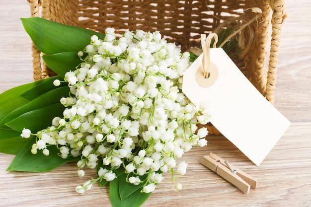 Lilly of the valley bloemen ruikertje in mand met lege papier opmerking op houten achtergrond