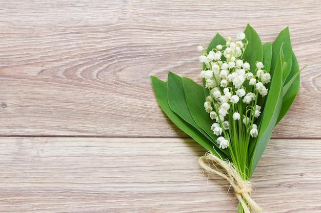 Lilly of the valley bloemen ruikertje op houten achtergrond met kopie ruimte