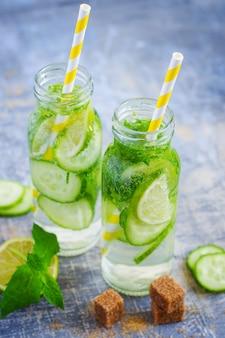 Limoen, komkommerlimonade in flessen met rietjes