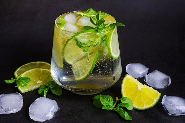 Limoen mojito in transparant glas op donkere achtergrond.