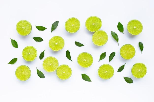 Limoenen met bladeren op wit wordt geïsoleerd.