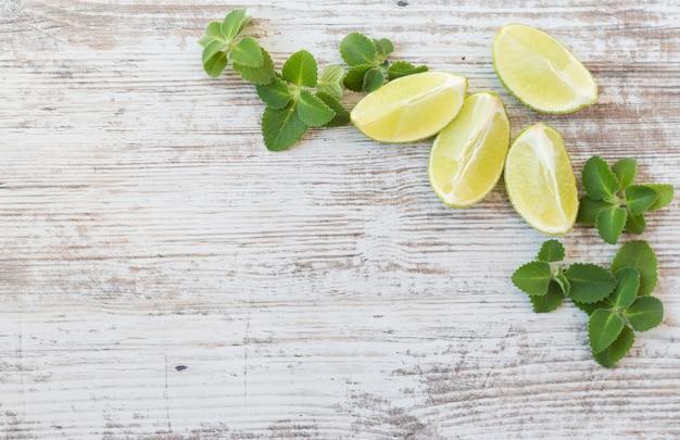 Limoenen met munt op witte oude tafel.
