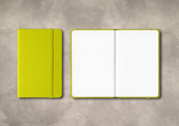 Limoengroen gesloten en open bekleed notitieboekjemodel dat op beton wordt geïsoleerd