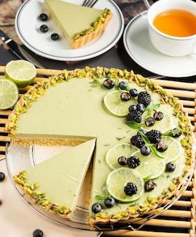 Limoenkaastaart gegarneerd met schijfjes limoen, bramen, zwarte bes en pistachenoten