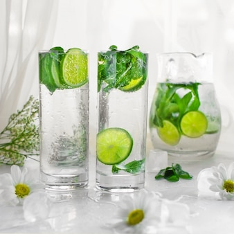 Limoenmojitoglazen met muntbladeren in wit