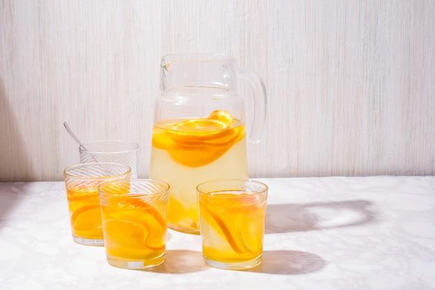 Limonade. drink met verse sinaasappels, citroenen en grapefruit. citroencocktail met sap en ijs. citruslimonade in glas jur.
