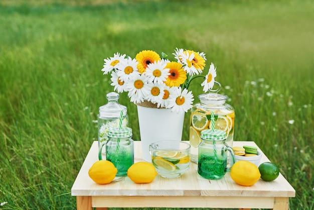 Limonade en daisy bloemen op tafel. mason jar glas limonade met citroenen. picknick buiten.