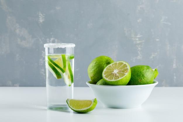 Limonade in een glas met citroenen zijaanzicht op wit en gips