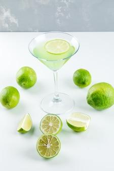 Limonade in een glas met uitzicht op de citroen hoge hoek op wit en gips