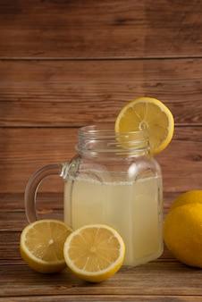 Limonade in een glazen beker op de houten tafel