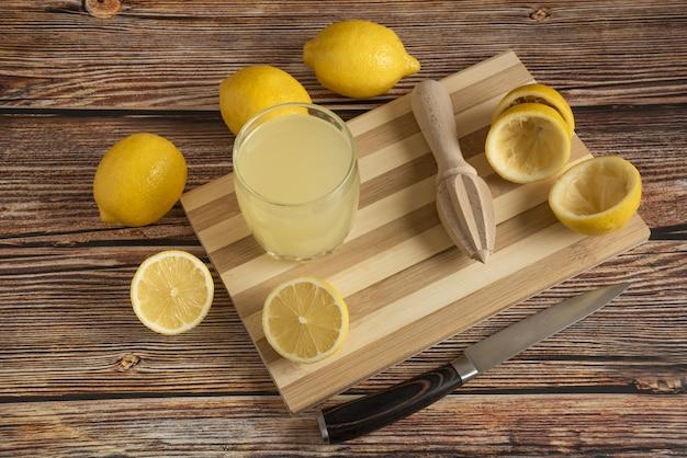 Limonade in een glazen beker op het houten bord