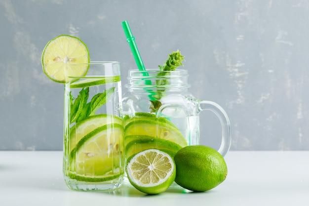 Limonade in glas en glazen pot met citroen, kruiden, stro zijaanzicht op wit en gips