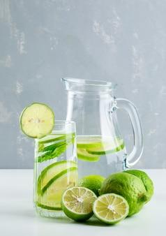 Limonade in glas en kruik met citroen, basilicum zijaanzicht op wit en pleister