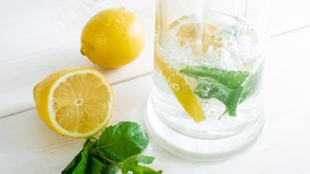 Limonade in glas en verse citroenhelften liggend op een wit houten bord.