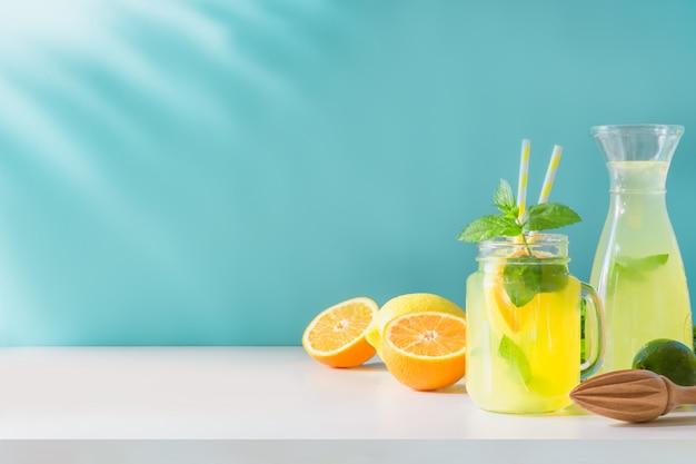 Limonade in metselaarkruik met citroen en munt op blauw. ruimte kopiëren.