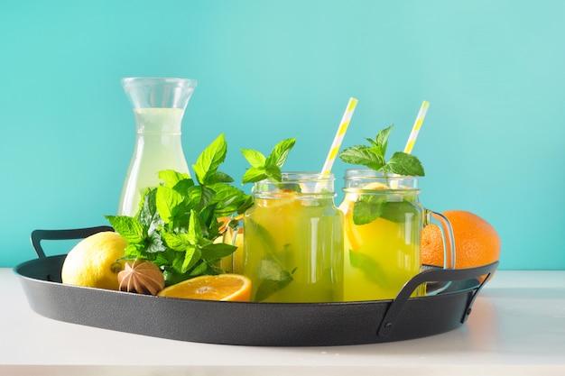 Limonade in metselaarkruik met citroen, sinaasappel en munt op blauw. ruimte kopiëren.