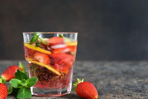 Limonade met aardbeien en munt op een donkere betonnen tafel.