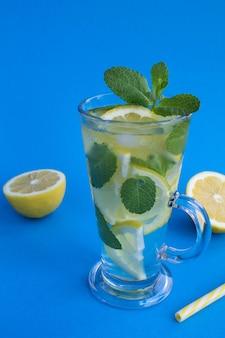 Limonade met citroen en munt in het glas op het blauwe oppervlak