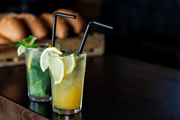 Limonade met citroen en munt op de achtergrond van vers gebakken broodjes in het café. zomer drankje