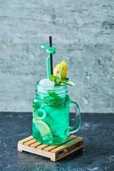 Limonade met citroen, ijs, stro en munt in het donkere oppervlak