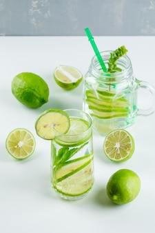 Limonade met citroen, kruiden, stro in glas en metselaarkruik op witte en grijze, hoge hoekmening.