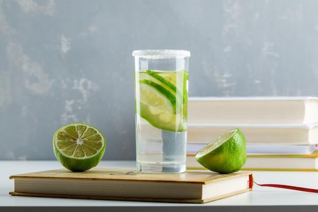 Limonade met citroen, schriften, boeken in een glas op wit en gips,