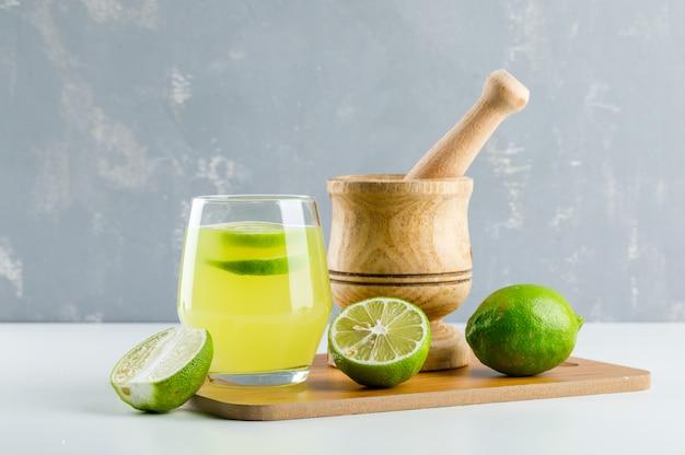 Limonade met citroen, vijzel en stamper, snijplank in een glas op wit en gips,