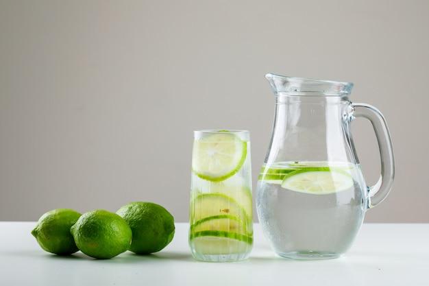 Limonade met citroenen in glas en kruik op wit en grijs,