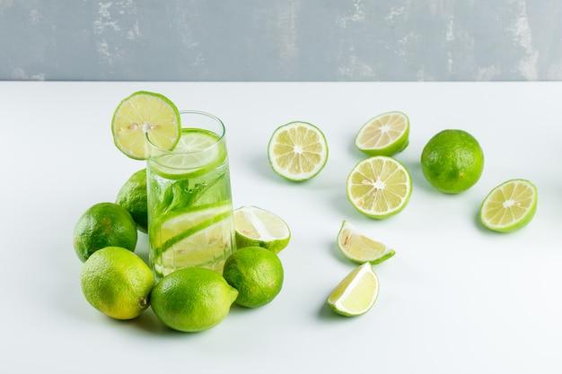 Limonade met citroenen, kruiden in een glas op wit en gips, hoge hoek bekeken.