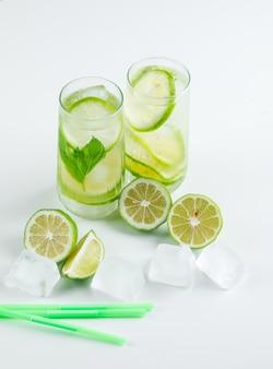 Limonade met citroenen, rietjes, basilicum, ijsblokjes in glazen op wit, hoge hoek bekeken.