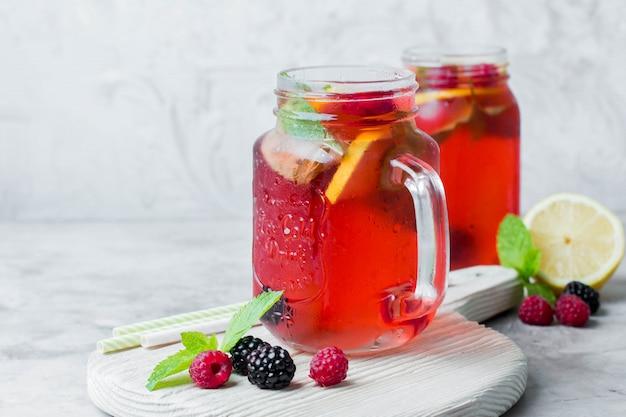 Limonade met framboos en blackberry met citroen, munt in metselaarkruik.