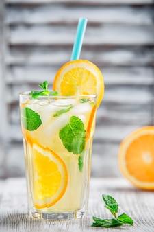 Limonade met sinaasappel en ijs op de witte achtergrond van het sjerpvenster