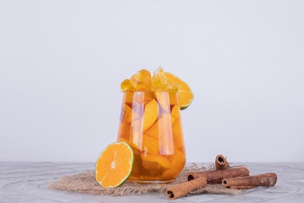 Limonade met stro, citroen en kaneel op wit