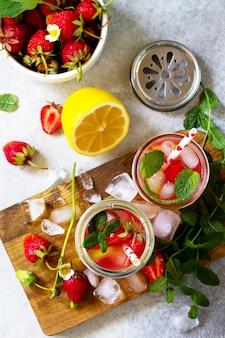 Limonade met verse frambozen, citroenen en ijs op een lichte stenen of leistenen tafel bovenaanzicht