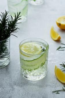 Limonade met verse komkommers, citroenen en rozemarijn in een bril op lichte achtergrond