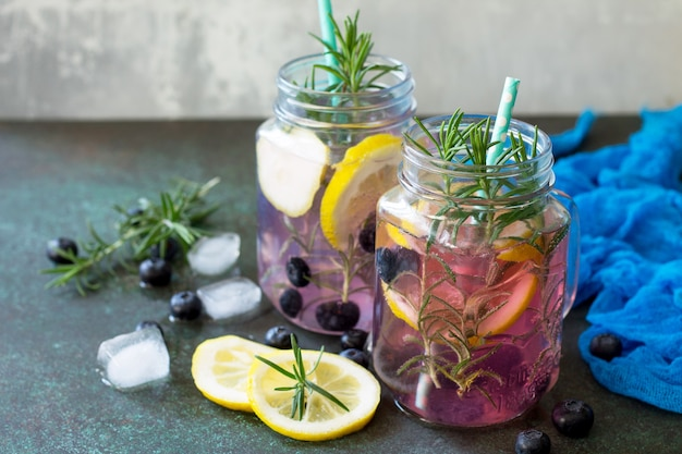 Limonade of cocktail met bosbessen en rozemarijn koud verfrissend drankje met ijs op tafel