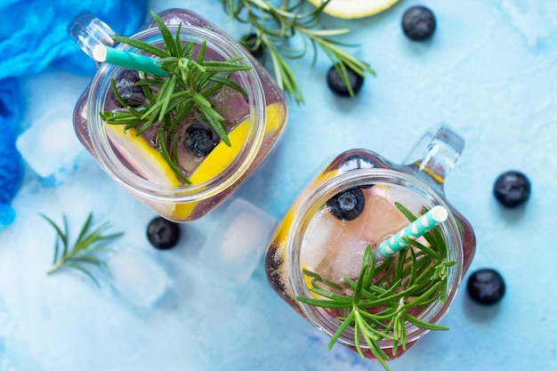 Limonade of cocktail met bosbessen en rozemarijn koud verfrissend drankje met ijs