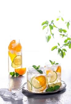 Limonade of mojito cocktail met sinaasappel en munt, koud verfrissend drankje of drank met ijs op grijze betonnen achtergrond