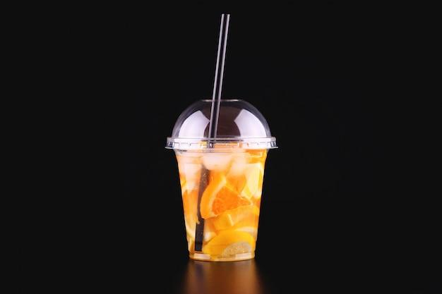 Limonade om te gaan beker met munt, sinaasappel en citroen op zwarte ruimte, geïsoleerd