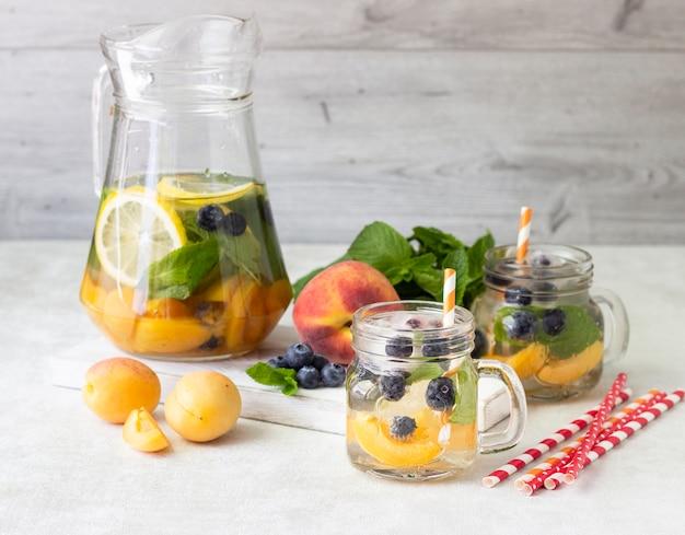 Limonade van abrikoos, bosbessen en verse munt in potten.