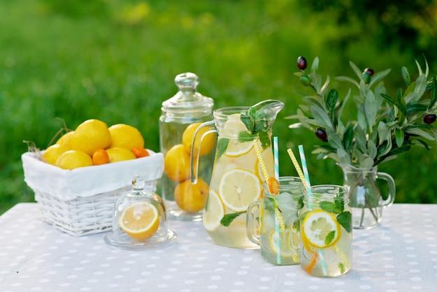 Limonade verfrissend drankje in een kruik en potten met citroenen, verse munt en ijs met een mand met citroenen en kumquat op een tuintafel. zomer buiten picknick. zachte selectieve focus.