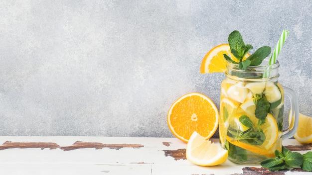 Limonadedrank van sodawater, citroen en muntbladeren in kruik op lichte achtergrond.