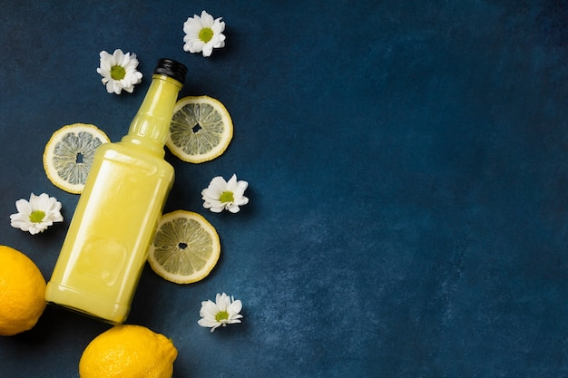 Limoncello fles met citroenen en bloemen op blauwe achtergrond bovenaanzicht