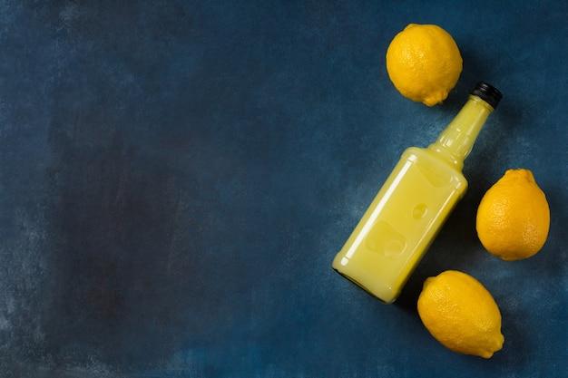 Limoncello fles met citroenen op blauwe achtergrond
