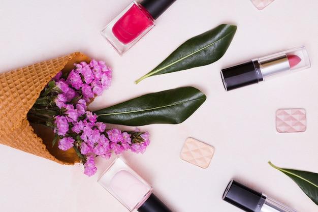 Limonium en blad in de wafelkegel; nagellakfles; lippenstift en oogschaduw op roze achtergrond